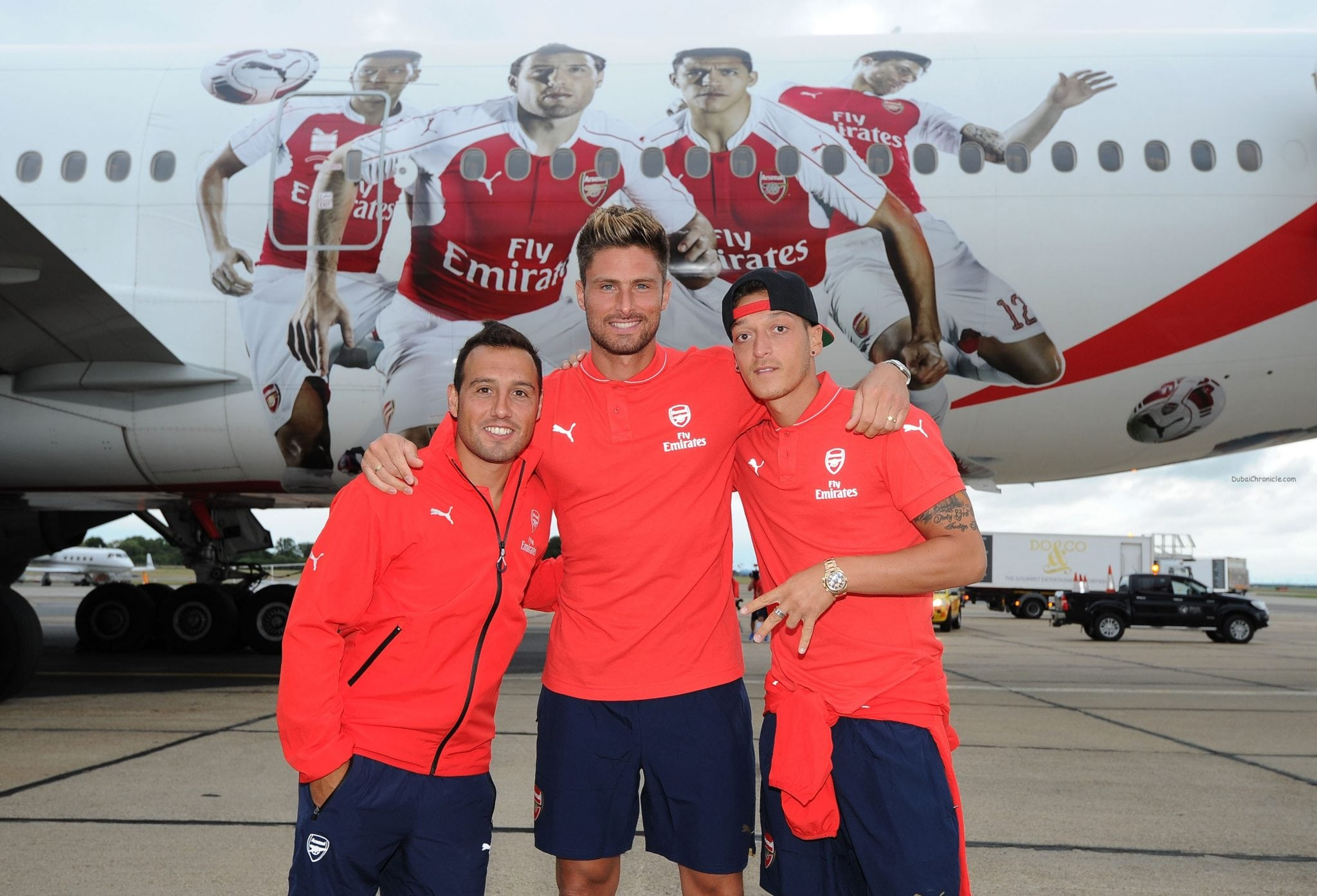 Santi Cazorla, Olivier Giroud and Mesut Ozil of Arsenal in front of their images on the Emirates plane at Stansted Airport on July 12, 2015 in London, England. (Photo by David Price/Arsenal FC via Getty Images) *** Local Caption *** Santi Cazorla; Olivier Giroud; Mesut Ozil